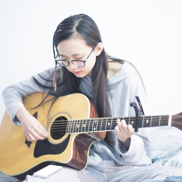 Girl playing the guitar and doing ear training